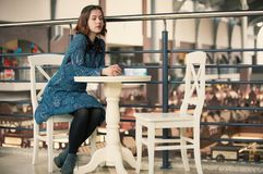 Portrait of a young dreamy woman sitting in the cafe. Portrait of a young dreamy pretty woman sitting in the street cafe Stock Image