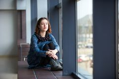Portrait of a young dreamy woman sitting on the window sill. Portrait of a young dreamy pretty woman sitting on the window sill Royalty Free Stock Images
