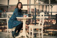 Portrait of a young dreamy woman sitting in the cafe. Portrait of a young dreamy pretty woman sitting in the street cafe Royalty Free Stock Photo