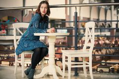 Portrait of a young dreamy woman sitting in the cafe. Portrait of a young dreamy pretty woman sitting in the street cafe Royalty Free Stock Photography