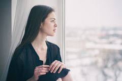 Portrait of a young dreamy woman sitting on the window sill. Portrait of a young beautiful dreamy woman sitting on the window sill Royalty Free Stock Image