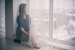 Portrait of a young dreamy woman sitting on the window sill. Portrait of a young beautiful dreamy woman sitting on the window sill Stock Image