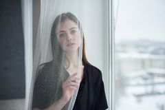 Portrait of a young dreamy woman sitting on the window sill. Portrait of a young beautiful dreamy woman sitting on the window sill Stock Photo