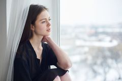 Portrait of a young dreamy woman sitting on the window sill. Portrait of a young beautiful dreamy woman sitting on the window sill Royalty Free Stock Images