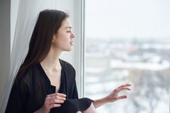 Portrait of a young dreamy woman sitting on the window sill. Portrait of a young beautiful dreamy woman sitting on the window sill Stock Photography