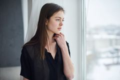 Portrait of a young dreamy woman sitting on the window sill. Portrait of a young beautiful dreamy woman sitting on the window sill Stock Photos