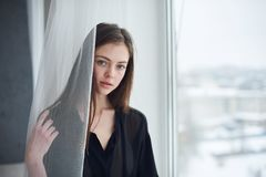 Portrait of a young dreamy woman sitting on the window sill. Portrait of a young beautiful dreamy woman sitting on the window sill Royalty Free Stock Photo