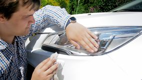 Portrait of young male driver cleaning car headlamps. Portrait of young driver cleaning car headlamps Royalty Free Stock Images