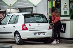 Portrait of young driver girl taking fuel in Intermarche gas Station stock images