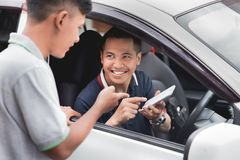 Driver showing his mobile phone to a man standing next to his ca. Portrait of young driver showing his mobile phone to a men standing next to his car. taxi Stock Image