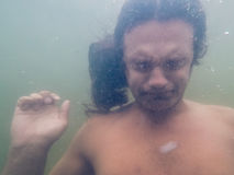 Portrait of a young Drowning man in sea water, underwater photo Royalty Free Stock Photography