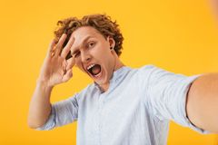 Portrait of young ecstatic man 20s taking selfie photo and showing ok sign with fingers, isolated over yellow background royalty free stock photography