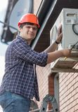 Portrait of young electrician repaiting outer unit of air conditioner. Portrait of electrician repaiting outer unit of air conditioner Royalty Free Stock Photos