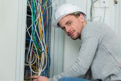 Portrait young electrician wiring electric panel. Portrait of young electrician wiring an electric panel Royalty Free Stock Photo