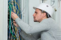 Portrait young electrician wiring electric panel. Portrait of young electrician wiring an electric panel Stock Images