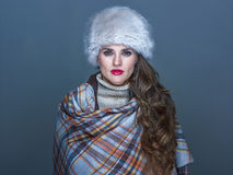Portrait of young elegant woman in fur hat isolated on cold blue. Winter things. Portrait of young elegant woman in fur hat isolated on cold blue background Royalty Free Stock Images