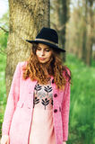 Portrait young elegant woman in pink coat and black hat. Fashion Stock Image