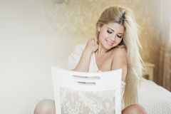 Portrait of young elegant woman sitting on chair in bedroom Stock Photos