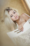 Portrait of young elegant woman sitting on chair in bedroom Royalty Free Stock Photo