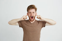 Portrait of young emotive angry man closing ears shouting screaming over white background. Copy space Stock Photography
