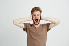 Portrait of young emotive angry man closing ears shouting screaming over white background. Copy space Stock Photo