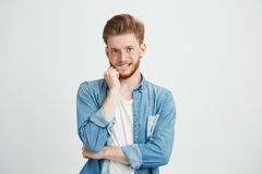 Portrait of young emotive handsome man looking at camera thinking with hand on chin biting lip over white background. Copy space Royalty Free Stock Photos