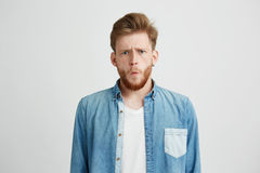 Portrait of young emotive shocked man frowning looking at camera over white background. Copy space Stock Photo