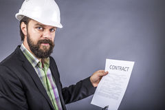 Portrait of young engineer with hardhat reading a contract Stock Photo