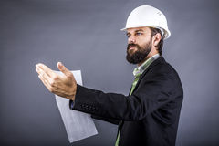 Portrait of young engineer holding plan drawings and explaining Stock Photography