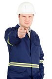 Portrait of young engineer pointing to the camera. Portrait of young engineer in overalls and helmet pointing to the camera isolated on white background Royalty Free Stock Images