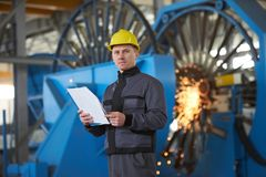Portrait of young engineer taking notes in factory warehouse roo. M. Industrial manufacturing worker reading documents Stock Photo
