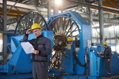 Portrait of young engineer taking notes in factory warehouse roo. M. Industrial manufacturing worker reading documents Stock Photography