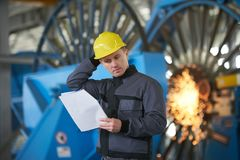 Portrait of young engineer taking notes in factory warehouse roo. M. Industrial manufacturing worker reading documents Stock Image