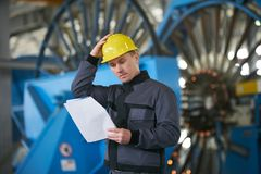 Portrait of young engineer taking notes in factory warehouse roo. M. Industrial manufacturing worker reading documents Royalty Free Stock Images