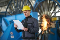 Portrait of young engineer taking notes in factory warehouse roo. M. Industrial manufacturing worker reading documents Stock Photos
