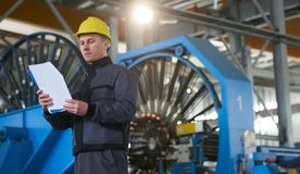 Portrait of young engineer taking notes in factory warehouse roo. M. Industrial manufacturing worker reading documents Royalty Free Stock Image