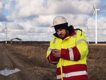 Portrait of young engineer working on mobile phone outdoors in helmet and reflective jacket Stock Image