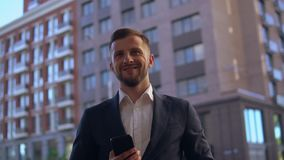 Portrait young entrepreneur outdoors. Successful businessman posing in city. handsome bearded man wearing elegant suit standing on the street looking camera with stock footage