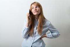 Portrait of young european lady with red hair, white skin and freckles. Dressed in casual blue shirt holding her phone next to her ear talking or listening to Stock Image