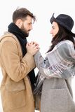 Portrait of young european man holding woman hand in white background, wearing coat with scarf. royalty free stock photography