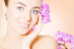 Portrait of young european woman with clear skin and purple orch Royalty Free Stock Images