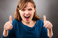 Portrait of a young excited woman holding his both thumbs up, vi Stock Images