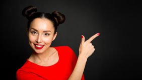 Portrait of young excited woman pointing forefingers over black Stock Photography