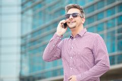 Portrait of young executive talking on the mobile phone outdoors. royalty free stock photos
