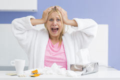 Portrait of young exhausted woman screaming while suffering from headache and cold in kitchen Stock Photography