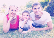 Portrait of young family with boy lying in park Stock Photo