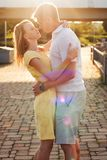 Portrait of a young family couple hugging kissing in the sunlight flecks. Young women in yellow dress and men are hugging kissing in the city park near the river royalty free stock photos