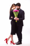 Portrait of young family couple in love with bouquet of lila tulips posing dressed in classic clothes on white backround. Man with beard in Suit, Woman in royalty free stock image
