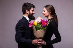 Portrait of young family couple in love with bouquet of multicolor tulips posing dressed in classic clothes on grey backround. Stock Image