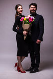 Portrait of young family couple in love with bouquet of multicolor tulips posing dressed in classic clothes on grey backround. Royalty Free Stock Images